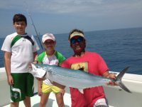 One boy one girl and fishing mate holding a cero mackerel