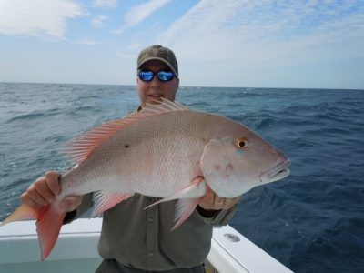 customer hold a mutton snapper on the southpaw fishing charter boat