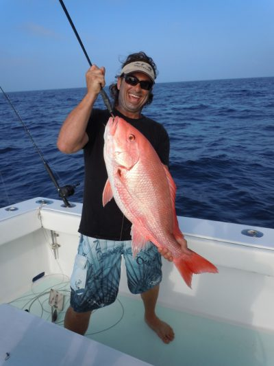 key west Fishing mate holding red snapper