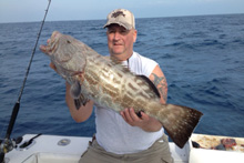 Man holding a black grouper on a fishing charter