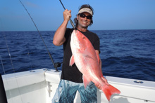 Fishing crew holding a red snapper