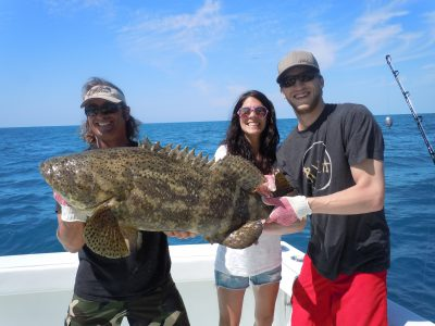 fishing charter holding a goliath grouper