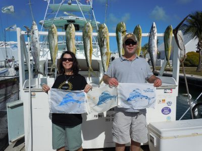 Couple with sailfish 3 catch and release flags and dolphin