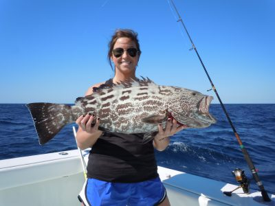 woman holding black grouper