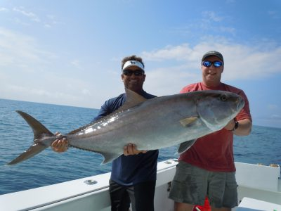 Fishing charter and crew holding greater amber jack