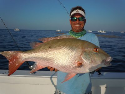 Fishing mate holding big mutton snapper