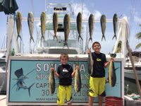 2 boys with 13 dolphin hanging on the fish rack