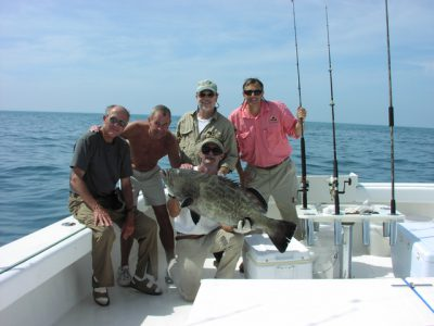 Fishing charter holding a black grouper