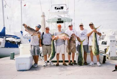 Group charter holding their catch at the dock.