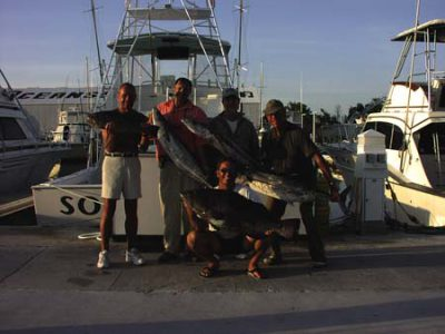 Group holding their fishing charter catch