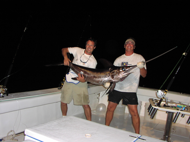 2 men holding a marlin