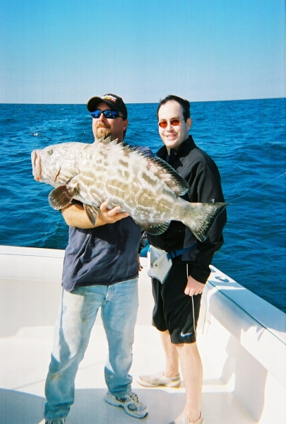 Mate and client holding a big black grouper